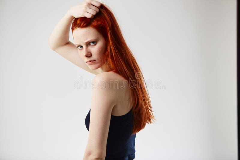 Het charmeren van roodharige langharig meisje gekleed in zwarte bovenkant en jeans houdt hand op haar hoofd op de witte achtergro royalty-vrije stock afbeeldingen