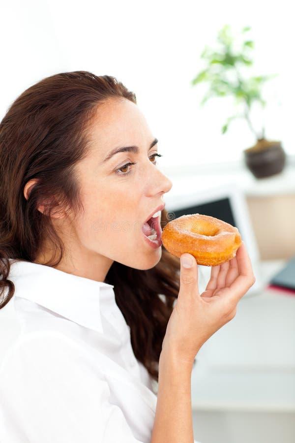 Het charmeren van Spaanse onderneemster die een doughnut eet stock foto's