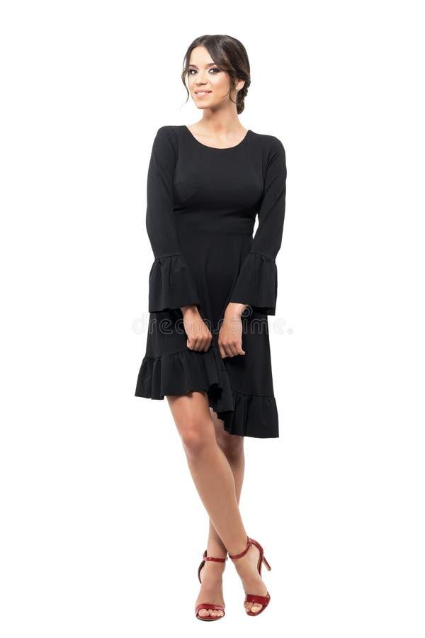 Het charmeren van Spaanse vrouw in zwarte kleding die en bij camera stellen glimlachen stock fotografie