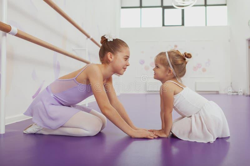 Het charmeren van twee jonge ballerina's die bij balletklasse praktizeren royalty-vrije stock fotografie