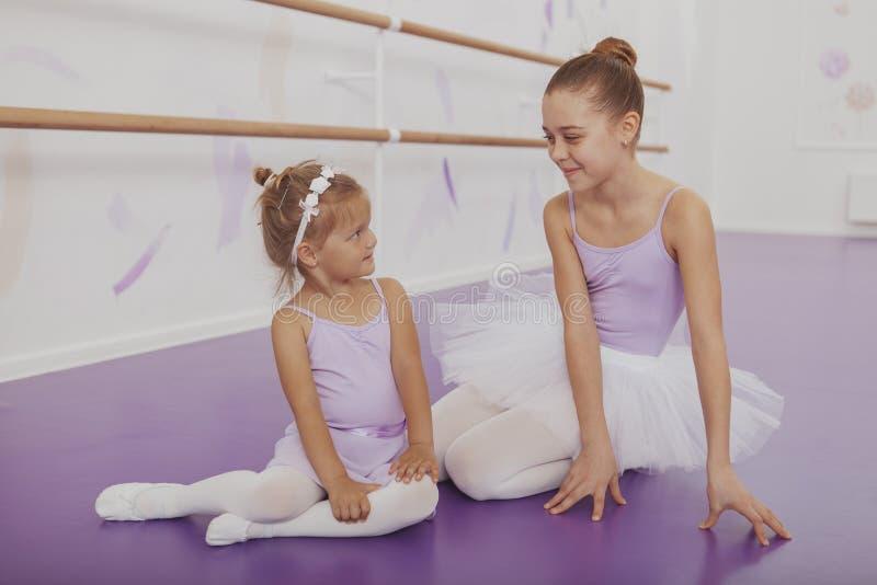 Het charmeren van twee jonge ballerina's die bij balletklasse praktizeren stock afbeeldingen