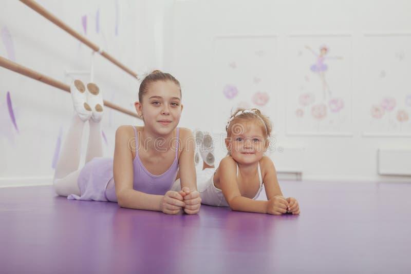 Het charmeren van twee jonge ballerina's die bij balletklasse praktizeren stock foto