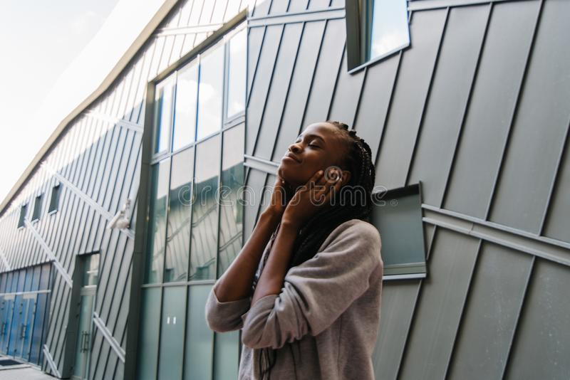 Het charmeren van vreedzaam Afrikaans meisje met lang haar geniet van muziek in oortelefoons Close-up zijportret royalty-vrije stock foto