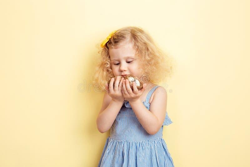 Het charmeren van weinig krullend meisje in de lichtblauwe kleding houdt weinig twee nesten met eieren op de achtergrond van gele royalty-vrije stock afbeelding