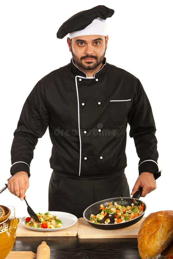 Het chef-kokmannetje schikt voedsel op plaat stock foto's