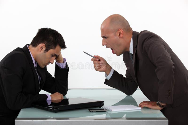 Het chef- schreeuwen bij werknemer stock foto's