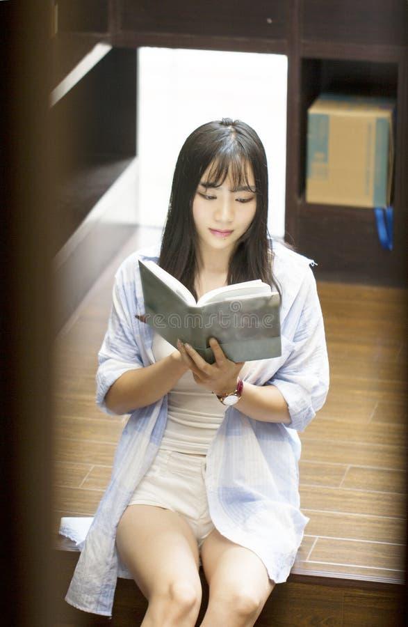 Het Chinese Portret van jonge mooie vrouw leest Boek in Boekhandel royalty-vrije stock afbeeldingen
