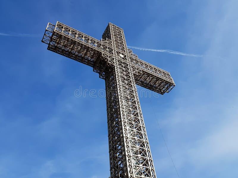 Het christelijke kruis van de metaalbouw met mooie blauwe hemelachtergrond stock foto's