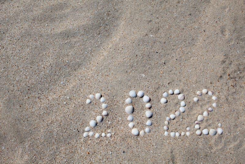 Het cijfer '2022 'wordt opgemaakt op zand met shells royalty-vrije stock fotografie
