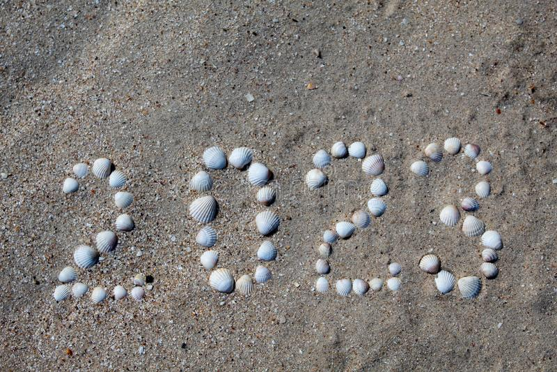 Het cijfer '2023 'wordt opgemaakt op zand met shells stock fotografie