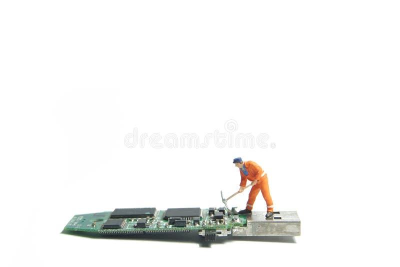 Het cijfer die van de technicusarbeider zich op een oude aandrijving van de usbflits bevinden IT steunconcept stock fotografie