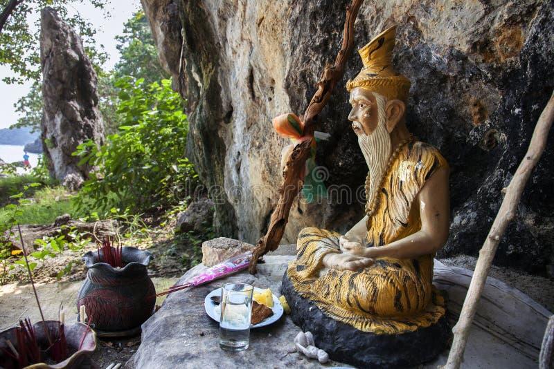 Het cijfer van een Boeddhistische monnik, en dienstenaanbod op het strand van t royalty-vrije stock afbeelding