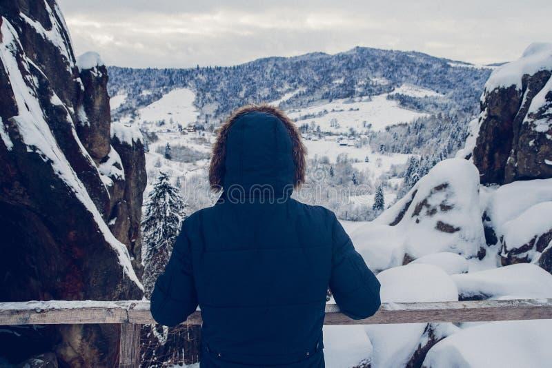 Het cijfer van een reiziger die aan een bergtop tegen de achtergrond van een snow-covered landschap stijgen, achtermening royalty-vrije stock fotografie