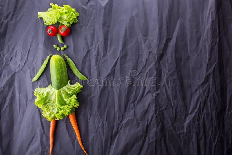 Het cijfer van het meisje met groenten op zwarte document achtergrond Gewichtsverlies en gezonde levensstijl stock foto's