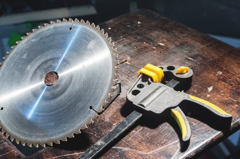 Het cirkelblad van een cirkelzaag ligt op een houten werkbank naast een klem op hout in een workshop van het timmermanshuis royalty-vrije stock foto