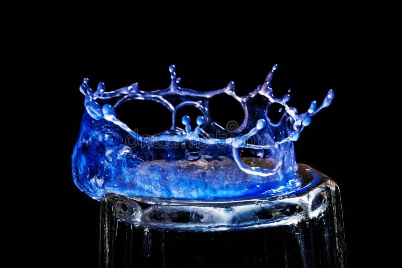 Het close-up een blauwe daling in de vorm van een kroon is verdeeld op het glas stock afbeeldingen