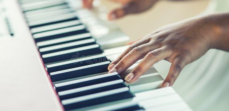 Het close-up een zwarte overhandigt het spelen op piano stock foto