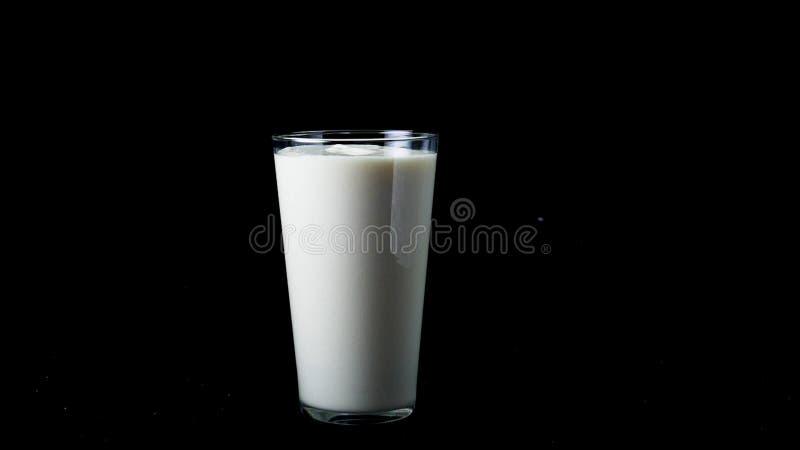 Het close-up in glas giet witte yoghurt Kader In transparant groot glas giet witte dikke vloeistof op geïsoleerde zwarte stock fotografie
