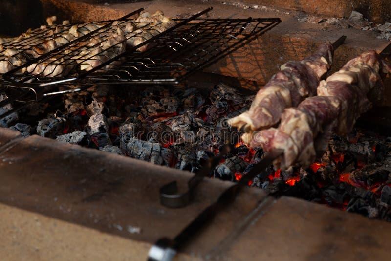 Het close-up op het proces om barbecue van varkensvlees of rundvleesvlees te koken zette op vleespennen in een grill met een knap royalty-vrije stock foto's