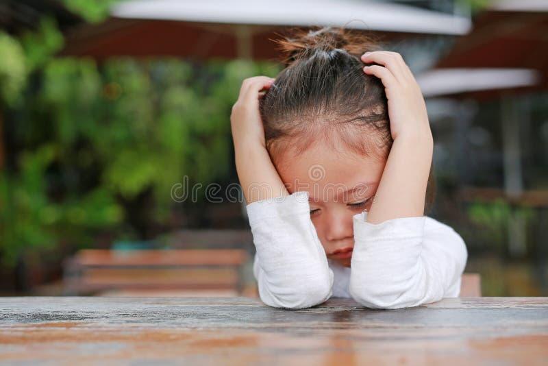 Het close-up van aanbiddelijk weinig Aziatisch kindmeisje drukte teleurstelling of ongenoegen op de houten lijst uit stock foto's