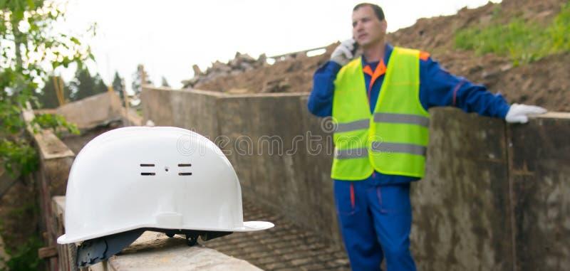 Het close-up van de helm, op de achtergrond, de ingenieur spreekt op de telefoon met de sponsor over de bouw van stock afbeelding