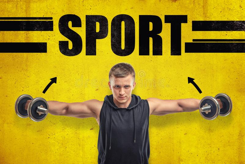 Het close-up van de jonge geschikte mens in sleeveless hoody doende zijzijde heft met domoren op tegen gele muur met titel royalty-vrije stock afbeelding