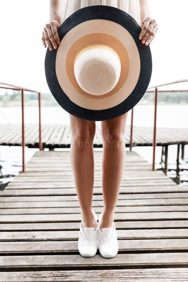 Het close-up van de strandhoed in de handen van een meisje op een brug stock afbeeldingen