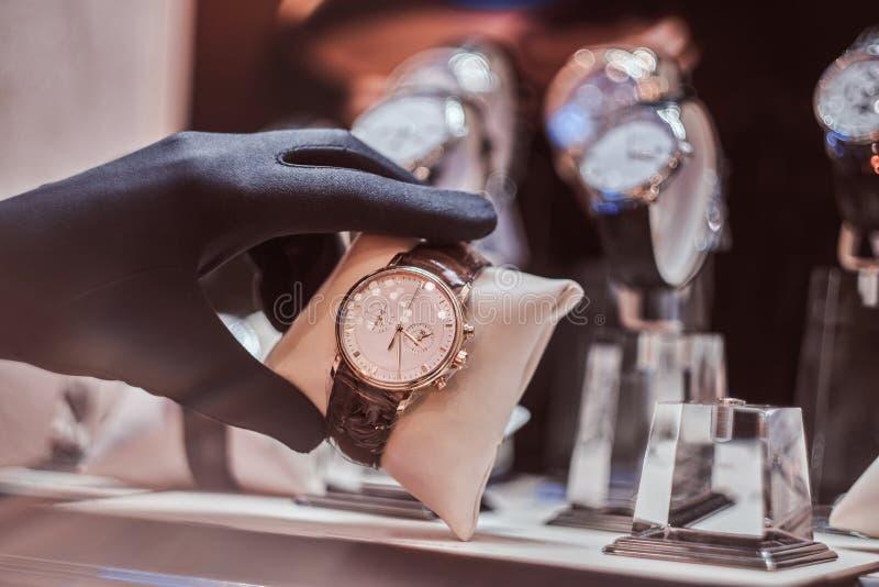 Het close-up van de verkoper dient handschoenen in toont het horloge van de exclusieve mensen van de nieuwe inzameling stock foto's