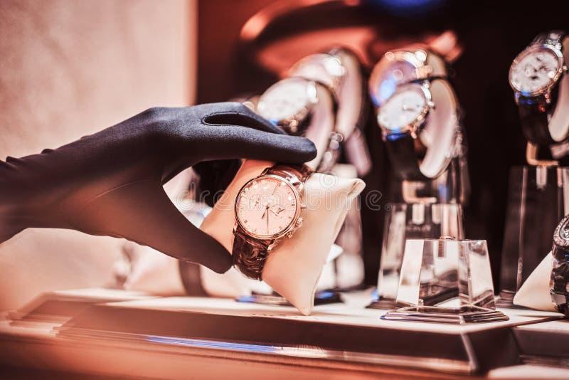 Het close-up van de verkoper dient handschoenen in toont het horloge van de exclusieve mensen van de nieuwe inzameling stock afbeeldingen