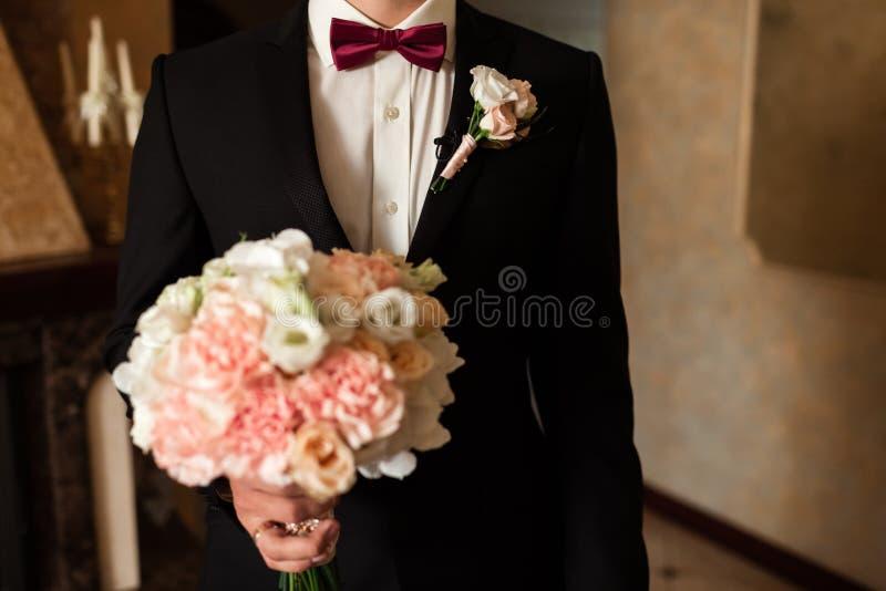 Het close-up van een bebouwd kader is een teder boeket van rozen in de handen van een bruidegom royalty-vrije stock foto's