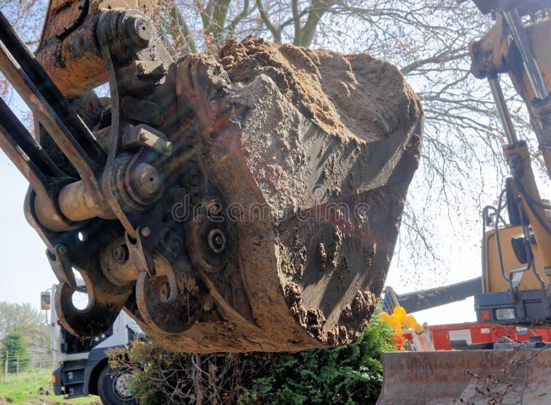 Het close-up van een grote graafwerktuigschop vulde met een machtige lading van los bruin zand bij de bouwwerf stock fotografie