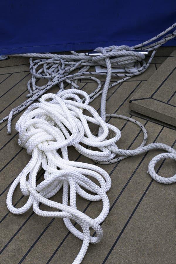 Het close-up van een meertroskabel met een geknoopt eind bond rond cleat op een houten kabel van de pijler Zeevaartmeertros royalty-vrije stock foto's