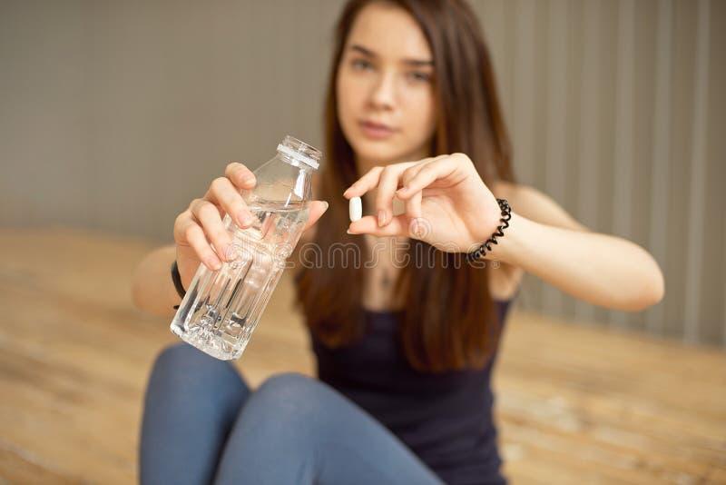 Het close-up van een meisje houdt een pil met sportenadditieven voor opleiding en een fles water royalty-vrije stock afbeelding