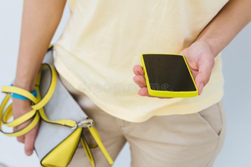 Het close-up van een meisje met een gele mobiele telefoon en het wijfje doen binnen in zakken stock foto's