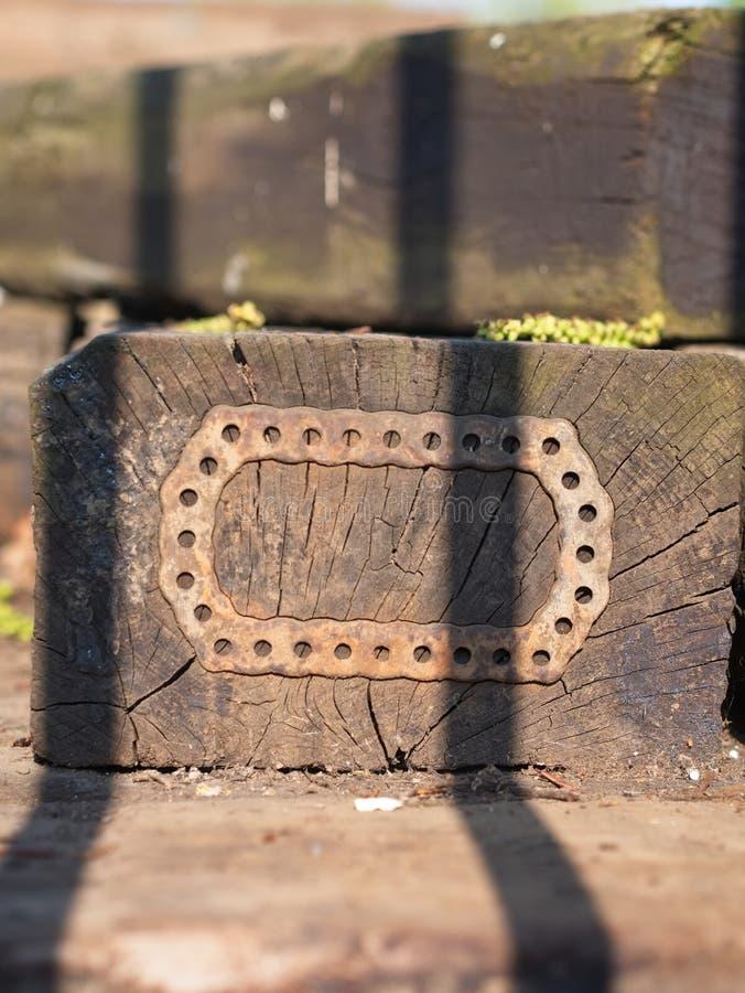 Het close-up van een oud blok van hout met een stuk van ijzer met gaten maakte op de oppervlakte vast stock afbeeldingen