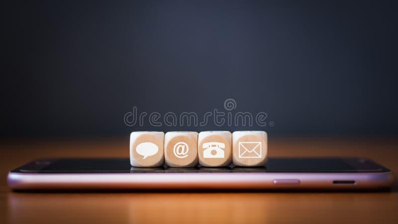 Het close-up van een telefoon, e-mail, praatje en het houten de postpictogrammen dobbelen het schikken op een rij op mobiele tele stock afbeeldingen