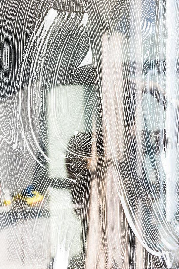 Het close-up van een vrouw in eenvormige en gele handschoenen wast vensters met vensterschraper Het professionele huis schoonmake stock foto's