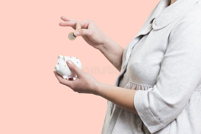 Het close-up van een vrouw zet muntstuk in spaarvarken Het concept van het Economgeld royalty-vrije stock foto