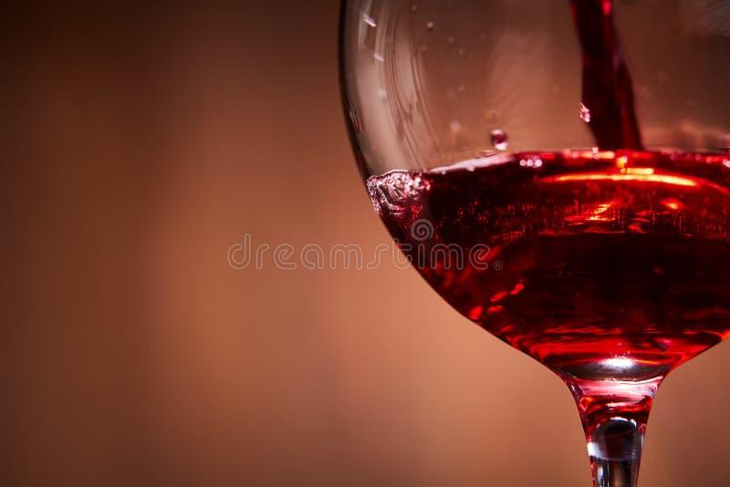 Het close-up van helder rode wijn goot in het wijnglas en het abstracte bespatten tegen bruine achtergrond stock foto
