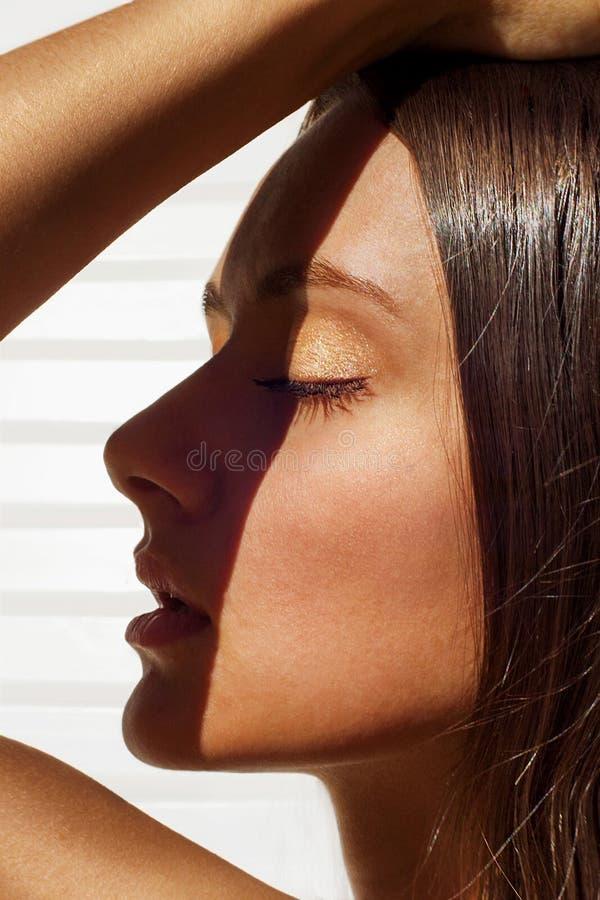 Het close-up van het manierportret van een jonge gelooide vrouw die in een witte chaise zitkamer zonnebaden royalty-vrije stock fotografie