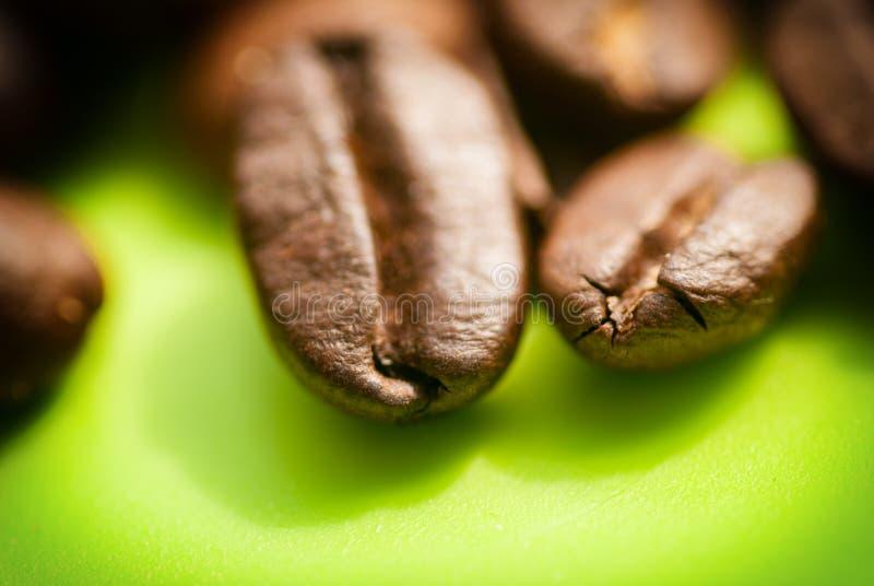 Het close-up van koffiebonen, macro op een groene achtergrond royalty-vrije stock afbeeldingen