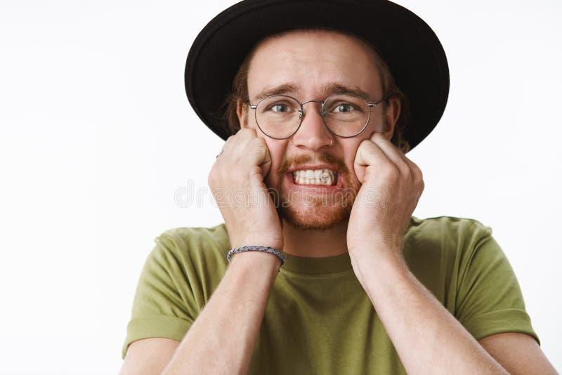 Het close-up van het panicking wordt geschoten, freaked uit intense jonge kerel dichtklemmend tanden die zich geschokte en bezorg stock afbeelding