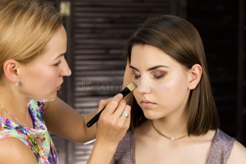 Het close-up van professionele grimeur die dagelijkse make-up doen, zet poeder op de wangen van de vrouw met borstel royalty-vrije stock foto's