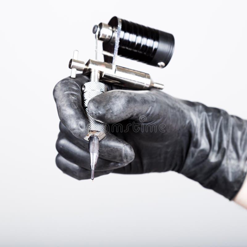 Het close-up van Tattooist dient zwarte handschoenen met tatoegeringsmachine in royalty-vrije stock foto