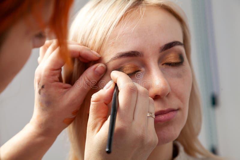 Het close-up van het toepassen van samenstelling in de salon op het model in de oosterse stijl, de grimeur legt gouden bruine sch stock foto