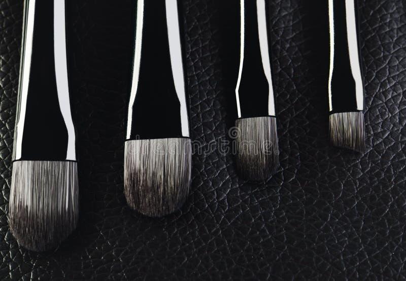 Het close-up van vier make-upborstels op een geweven zwarte leerbackgro royalty-vrije stock fotografie