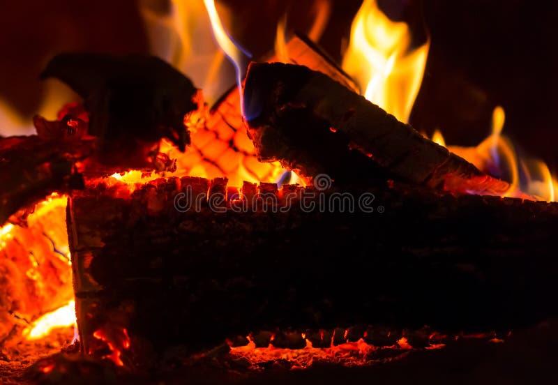 Het close-up van het vlammen oranje roodgloeiend logboek vuur als achtergrond in de donkere steenkolen helder in het ontwerp van  royalty-vrije stock foto's