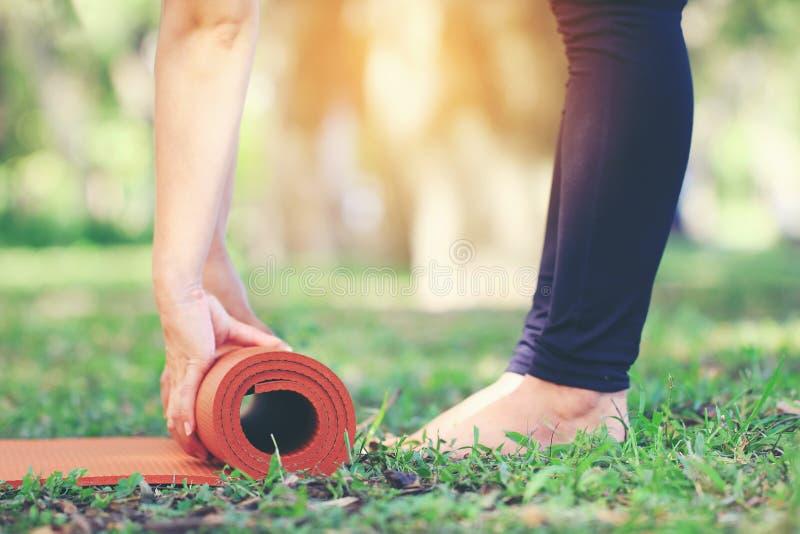 Het close-up van vrouw houdt yogamat voor mediteren in aard, Gezond levensstijlconcept te ontspannen stock afbeeldingen