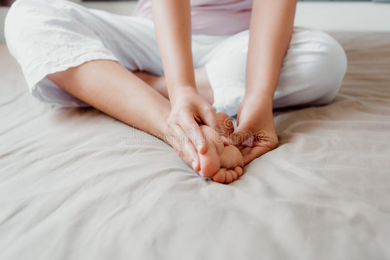 Het close-up van Vrouwenhanden masseert Haar Voeten op Slaapkamer, Jonge Volwassen die Benenpijn na het Huiswerk heeft Gezondheid stock foto
