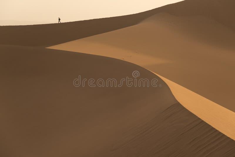 Het close-up van zandduinen en een klein het lopen mensencijfer stock fotografie